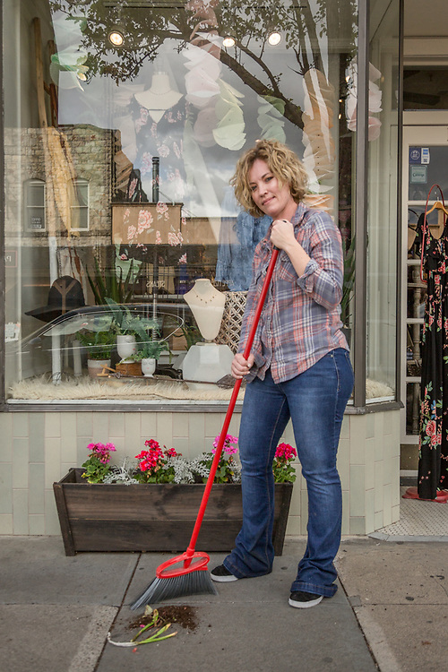 Rove co-owner Jessica Maas cleans up after planting geraniums outside her store on Lincoln Avenue in Calistoga.