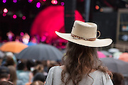A woman wearing a western straw hat watching Jason Walker at Celebrate Brooklyn. The umbrellas in the audience were raised several times during the evening when a light rain fell.