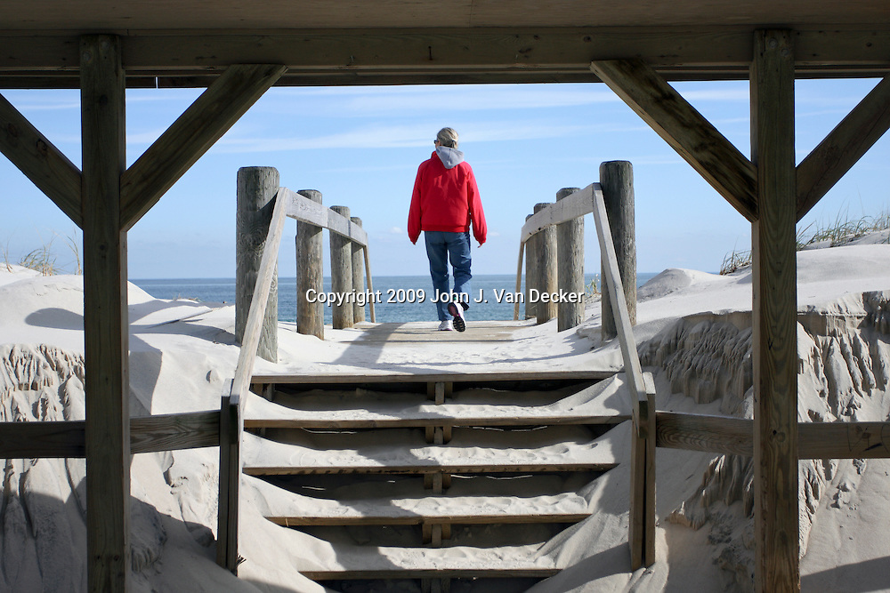 Woman walking on to beach through shelter, Lavalette, NJ