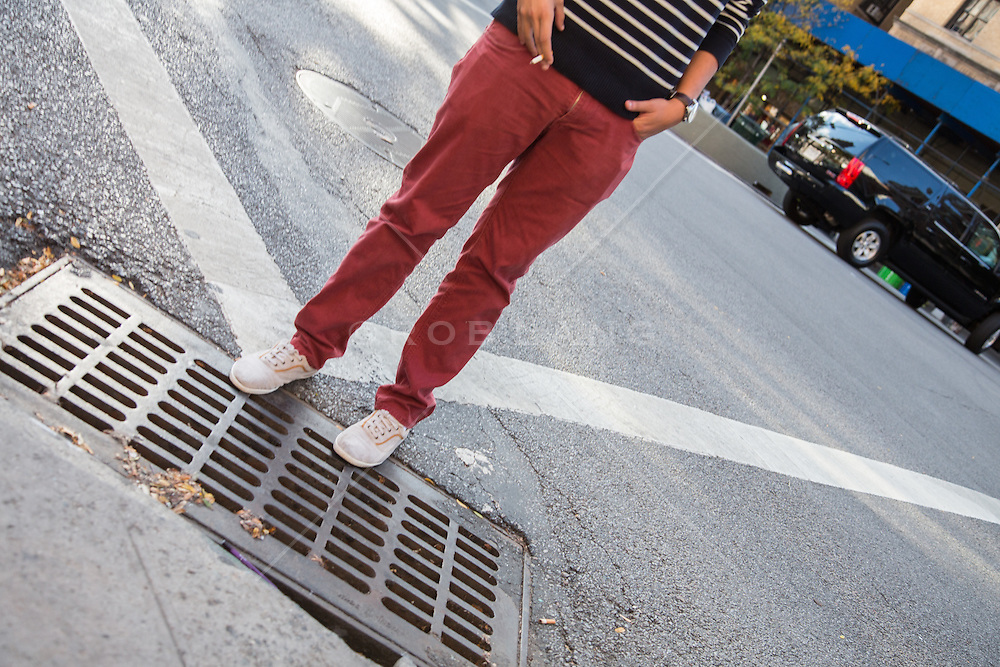 person walking over a city drain in New York City