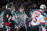 KELOWNA, CANADA - DECEMBER 30: Linesman Dustin Minty gets between players of the Prince George Cougars and the Kelowna Rockets  on December 30, 2014 at Prospera Place in Kelowna, British Columbia, Canada.  (Photo by Marissa Baecker/Shoot the Breeze)  *** Local Caption *** Dustin Minty;