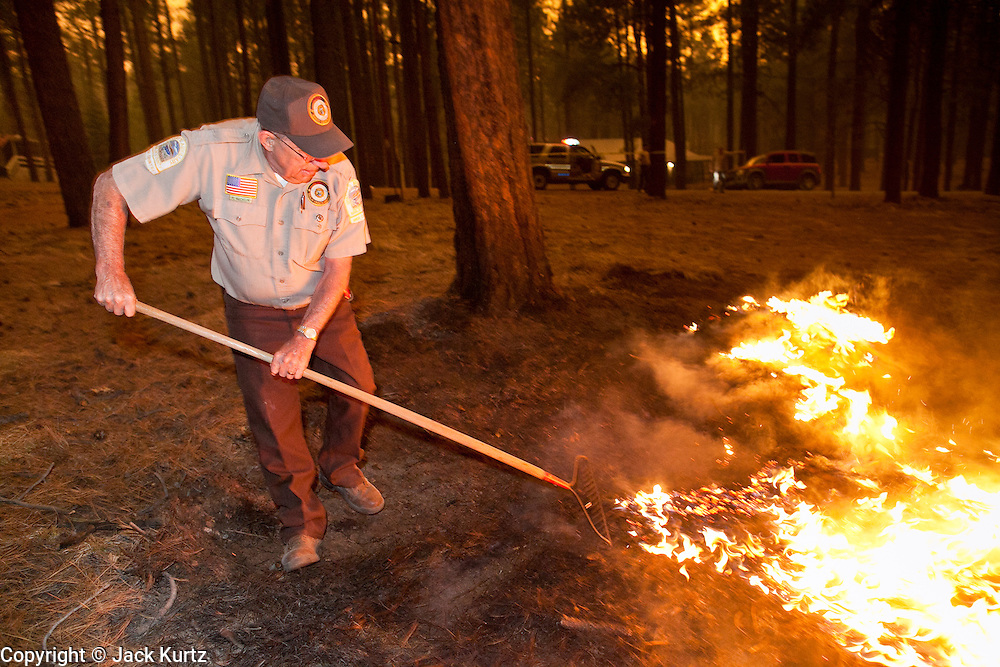 02 JUNE 2011 - ALPINE, AZ: Dick Bucklin, a volunteer with the Apache County SO attacks a spot fire in the Chapache development at the Wallow Fire near Alpine. High winds and temperatures complicated firefighters' efforts to get the blaze under control. Officials have issued a mandatory evacuation order and residents of the Alpine area had to leave by 8PM Thursday.   PHOTO BY JACK KURTZ