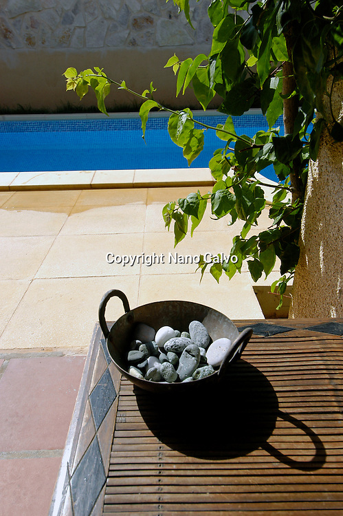 Stones and plates decorating a table, in the backyard of an ibizan house, Ibiza, Balearic Islands, Spain
