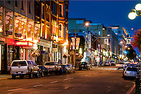 Lower Johnson Street glows at night with lights that highlight the historical architecture of the buildings.