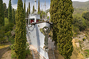Regia Nave Puglia, a warship, with Victory figurehead by Renato Brozzi, set into the Mastio hill, at Vittoriale degli italiani, or The Shrine of Italian Victories, the home, estate and museums of Gabriele D'Annunzio, 1863-1938, Italian writer, soldier and fascist, at Gardone Riviera, Lake Garda, Brescia, Lombardy, Italy. The ship was a gift from Admiral Thaon di Revel in 1923, in memory of captain Tommaso Gulli, who died in the waters of Split in 1920. Inside the ship is the Onboard Museum, opened 2002, with models of warships belonging to Duke Amedeo d'Aosta. The estate consists of the Prioria, where d'Annunzio lived 1922-38, an amphitheatre, the protected cruiser Puglia, the MAS vessel used by D'Annunzio in 1918 and a mausoleum. It is part of the Grandi Giardini Italiani. Picture by Manuel Cohen