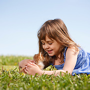Girl in sundress lying down on grass smiling face to face with tabby kitten