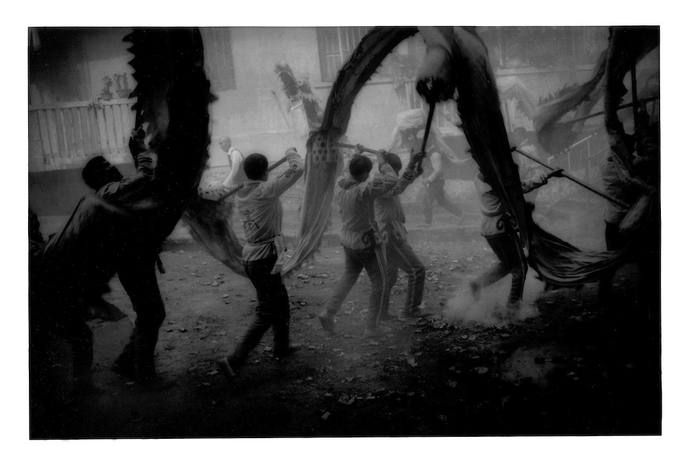 Firecrackers rain down on a dragone dance, Chinese New Year festival.  Yangshuo, Guangxi Province, China.  1998