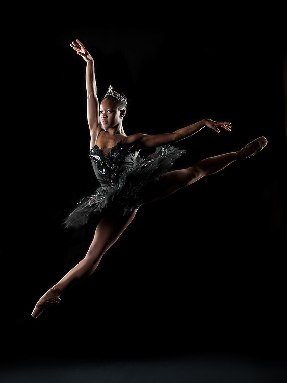 Black swan ballerina, Michaela dePrince, jumping in a black tutu against a black background. Photographed by Rachel Neville in New York City.