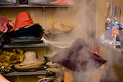 A hat body, shaped with only a suggestion of a crown and brim, on a rack over a steam generator, being steamed prior to shaping.