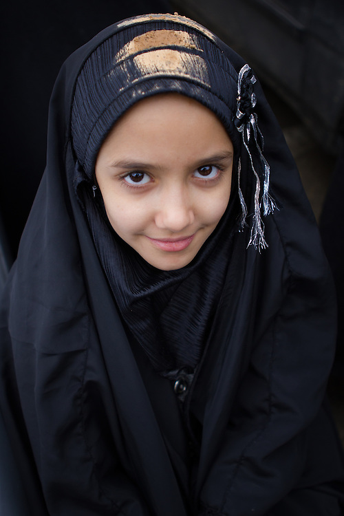 A young muslim girl, wearing a traditional black chador, partly covered with mud, mourning on the Day of Ashura in Bijar, Iran.