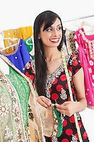 Attractive Indian female dressmaker looking away while working on an outfit