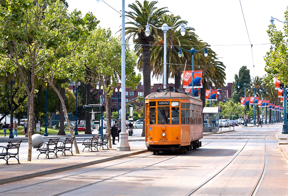 San Francisco, CA:  A Peter Witt vintage trolley from Milan rolls down the F-Line that loops and links Market Street, the Ferry Building, and Fishermen's Wharf.  <br /> <br /> From the Market Street Railway website: &quot;In addition to its world-famous cable car fleet, the San Francisco Municipal Railway (Muni) owns some ninety historic streetcars, trolleys, and trams (names used in different parts of the world to describe electric rail vehicles capable of running on city streets). About half of these streetcars are in active service, or being prepared for it; the remainder are currently non-operational, unrestored cars that could be used for future service expansion.<br /> <br /> Three general types of vintage streetcars are used in San Francisco: a collection of unique vintage cars from both San Francisco and around the world; streamlined art deco PCC streetcars from the 1940s and 1950s that provide the backbone of daily service; and 1920s Peter Witt trams from Milan, Italy, which also operate daily. <br /> <br /> This older type of streetcar was designed by Cleveland transit leader Peter Witt and ran in many US cities, though never in San Francisco. Milan, Italy built hundreds of Peter Witts in 1928 and are still running some today. Muni got one car, No. 1834, as a Trolley Festival gift in 1984 and liked it so much they obtained ten more in 1998 to meet the huge F-line rider demand.<br /> <br /> The Peter Witts entered Muni service still wearing the solid orange livery used in Milan for the past quarter-century. In 2004, however, car No. 1811 was repainted into the original 1928 Milan livery of yellow and white with black trim. In 2007, No. 1818 received the two-tone green livery that the Milan trams wore from the 1930s to the 1970s. Market Street Railway has suggested to Muni that as these cars are repainted, the fleet is balanced between the three historic Milan liveries (yellow, green, and orange). <br /> <br /> Some of the Milan trams retain their original M