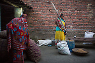Vegetable farmer Poonam Devi (in yellow), 40, a member of a Farmer's Producer Group, pounds grains at her home before heading out to her field in Machahi village, Muzaffarpur, Bihar, India on October 27th, 2016. Non-profit organisation Technoserve works with women vegetable farmers in Muzaffarpur, providing technical support in forward linkage, streamlining their business models and linking them directly to an international market through Electronic Trading Platforms. Photograph by Suzanne Lee for Technoserve