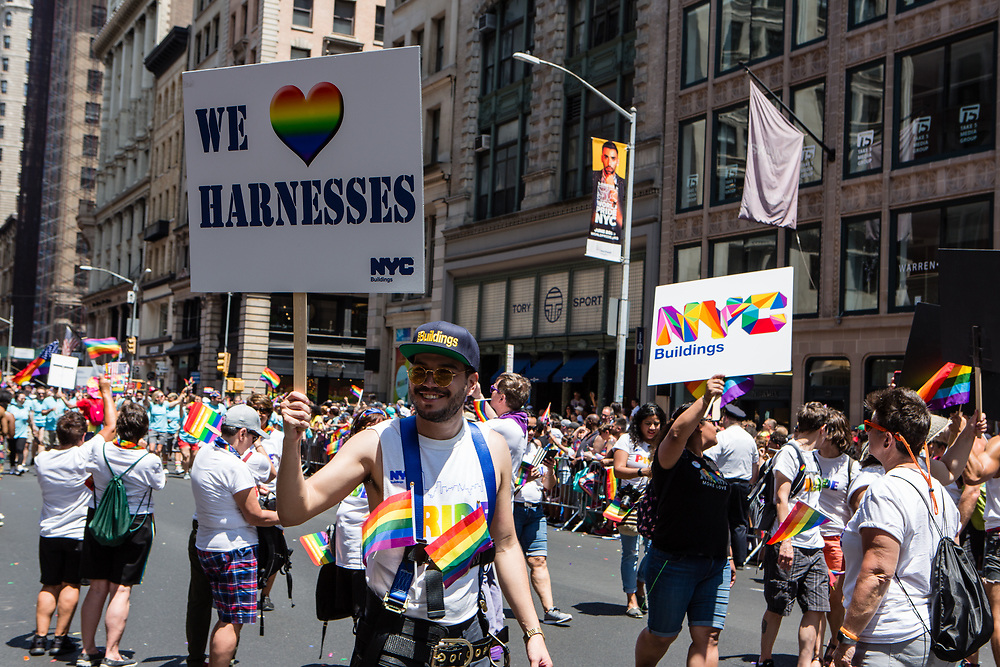 "New York, NY - 30 June 2019. The New York City Heritage of Pride March filled Fifth Avenue for hours with participants from the LGBTQ community and it's supporters. A grop from NYC Buildings, one of whom carries a sign reading ""We [rainbow colored heart] Harnesses."""