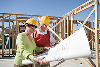 Senior man and woman examining blueprint in construction site