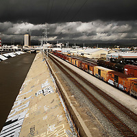 Box cars rest along the Los Angeles River in industrial LA.