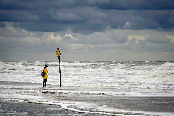 Nederland, the netherlands, egmond aan zee , 27-8-2018Een vrouw die langs het strand wandelt kijkt naar een waarschuwingsbord voor de mui, een verraderlijke onderstroom, stroming, die mensen kan laten verdrinken .Foto: Flip Franssen