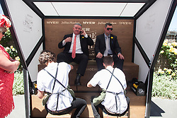 © Licensed to London News Pictures. 5/11/2013. Two racegoers get their shoes shined by shoe shiners during Melbourne Cup Day at Flemington Racecourse on November 5, 2013 in Melbourne, Australia. Photo credit : Asanka Brendon Ratnayake/LNP