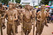 28 JUNE 2014 - DAN SAI, LOEI, THAILAND: Men covered in mud from the Mun River walk in the Ghost Festival parade in Dan Sai. Phi Ta Khon (also spelled Pee Ta Khon) is the Ghost Festival. Over three days, the town's residents invite protection from Phra U-pakut, the spirit that lives in the Mun River, which runs through Dan Sai. People in the town and surrounding villages wear costumes made of patchwork and ornate masks and are thought be ghosts who were awoken from the dead when Vessantra Jataka (one of the Buddhas) came out of the forest.    PHOTO BY JACK KURTZ