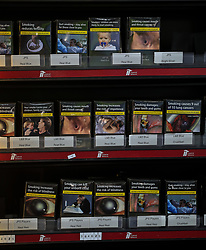 Cigarettes and tobacco for sale in a corner shop in Liverpool in standardised packaging bearing graphic warnings of the dangers of smoking, as rules designed to prevent young people taking up the habit come into full effect this weekend.