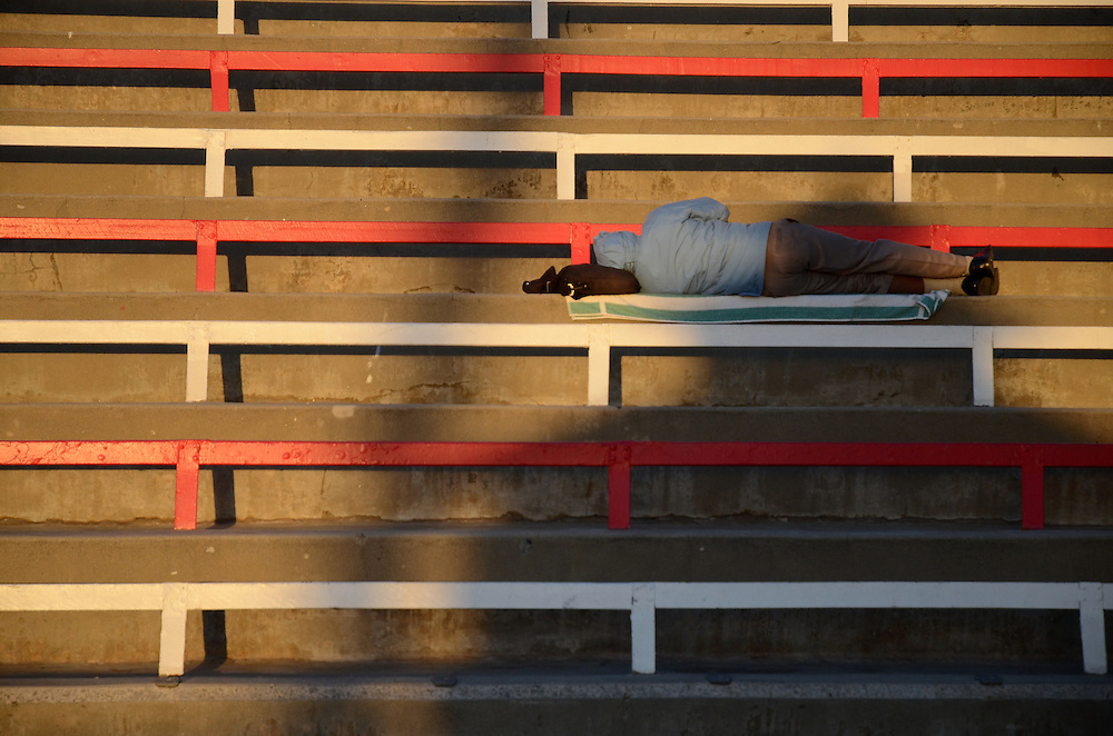 Man sleeping on red and white bleachers in Oceaside, CA. USA