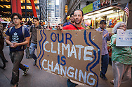 New York City, NY, Sept 27th 2011,A  participant of the Occupy Wall Street protest movement in Zuccotti Park  ( also know as Liberty Square) marches around the park holding a sign to bring attention to climate change. The protesters set up and encampment in Liberty Square inspired by the Egyptian Tahrir Square uprising . 80 people were arrested on Sept. 24th when the police clashed with the protesters near Union Square Park shining international media attention fueled by social media.