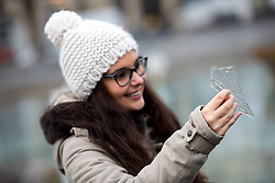 © Licensed to London News Pictures. 23/01/2017. London, UK. A couple photograph the ice in the Trafalgar Square fountains, which have frozen over this morning. Temperatures in London dropped to -2 degrees celsius last night, and the city is covered in thick low-lying fog. Photo credit : Tom Nicholson/LNP