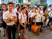 """13 FEBRUARY 2019 - SIHANOUKVILLE, CAMBODIA: Cambodian workers at the BWin Casino, a newly opened casino in downtown Sihanoukville, line up for a debriefing at the end of their overnight shift at the casino. There are about 80 Chinese casinos and resort hotels open in Sihanoukville and dozens more under construction. The casinos are changing the city, once a sleepy port on Southeast Asia's """"backpacker trail"""" into a booming city. The change is coming with a cost though. Many Cambodian residents of Sihanoukville  have lost their homes to make way for the casinos and the jobs are going to Chinese workers, brought in to build casinos and work in the casinos.      PHOTO BY JACK KURTZ"""