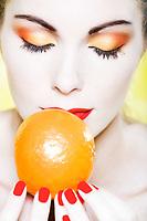 beautiful caucasian woman portrait smelling a mandarin in sutdio