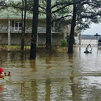 Grant Belhumeur kayaks to dry ground from a river house at the end of Rye Road, just outside of Aberdeen. Waters on Aberdeen Lake rose during the weekend, causing flooding concerns in some riverside neighborhoods.
