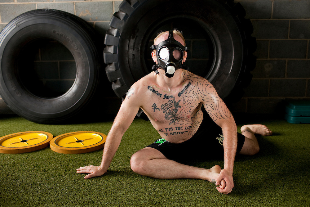 Mixed martial arts fighter Joey Carroll trains with a gas mask that restricts his oxygen intake to increase his breath strength, Charlotte, N.C., May 22, 2010.