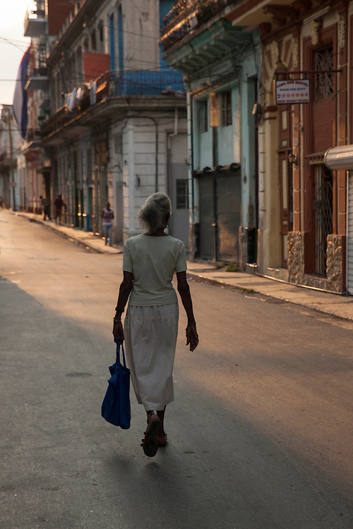An old elegant woman strolls down a street in Centro Habana at sunset, in Havana, Cuba.