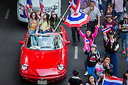 22 DECEMBER 2013 - BANGKOK, THAILAND:  Thai protestors in an Alfa Romeo sports car drive down Phloen Chit Road during an anti-government protest in Bangkok. Hundreds of thousands of Thais gathered in Bangkok Sunday in a series of protests against the caretaker government of Yingluck Shinawatra. The protests are a continuation of protests that started in early November and have caused the dissolution of the Pheu Thai led government of Yingluck Shinawatra. Protestors congregated at home of Yingluck and launched a series of motorcades that effectively gridlocked the city. Yingluck was not home when protestors picketed her home.    PHOTO BY JACK KURTZ