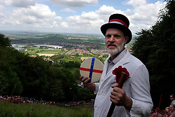 UK ENGLAND COOPERS HILL 31MAY04 - Master of Ceremonies Rob Seex, who has held his function since 1990, poses for a photo with a 7-pound Gloucester Cheese on top of a steep 200-metre slope. The cheese rolling is one of the oldest customs to have survived some saying, for hundreds of years, even pre-Roman times. The ceremony is reported to.have taken place originally at midsummer and to have been moved to Whitsun in early Saxon times. Some say it is a relic of an old heathen festival to celebrate the return of spring and.others say, when held in midsummer, it represented the waning of the sun as summer reached its height, but no one knows for sure....jre/Photo by Jiri Rezac..© Jiri Rezac 2004..Contact: +44 (0) 7050 110 417.Mobile:  +44 (0) 7801 337 683.Office:  +44 (0) 20 8968 9635..Email:   jiri@jirirezac.com.Web:     www.jirirezac.com