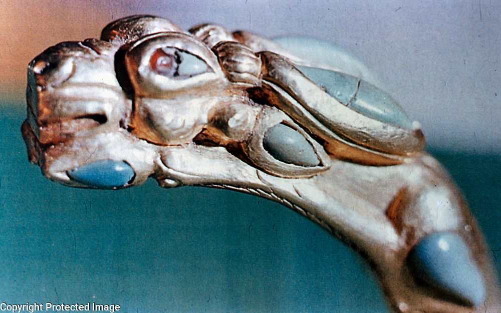 1981<br /> The affinity of these people with the wild animals of the steppe is impressively evident in a pair of bracelets with racing antelopes worn by the lady in Burial 2 (8.5 x 6.3; weight 254.37 grams). These magnificent antelopes, legs spread flat, muzzles resting on the hooves, have garnet and cornelian pupils bulging with the effort of great speed. A profusion of turquoise inlays adds to the charm of these bracelets. <br /> Photo: Louis Dupree
