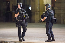 © Licensed to London News Pictures. 23/05/2017. Manchester, UK. Armed police search and clear Cathedral Gardens ahead of carrying out a controlled explosion . Police and other emergency services are seen near the Manchester Arena after reports of an explosion. Police have confirmed they are responding to an incident during an Ariana Grande concert at the venue. Photo credit: Joel Goodman/LNP