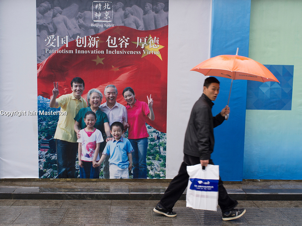 man walking past patriotic propaganda billboard in Beijing China