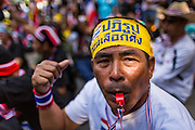"""14 JANUARY 2014 - BANGKOK, THAILAND: An anti-government protestor at Thai Royal Police Headquarters. Hundreds of protestors picketed police headquarters because they accuse the police of siding with the government during the protests. Tens of thousands of Thai anti-government protestors continued to block the streets of Bangkok Tuesday to shut down the Thai capitol. The protest, """"Shutdown Bangkok,"""" is expected to last at least a week. Shutdown Bangkok is organized by People's Democratic Reform Committee (PRDC). It's a continuation of protests that started in early November. There have been shootings almost every night at different protests sites around Bangkok, but so far Shutdown Bangkok has been peaceful. The malls in Bangkok are still open but many other businesses are closed and mass transit is swamped with both protestors and people who had to use mass transit because the roads were blocked.     PHOTO BY JACK KURTZ"""