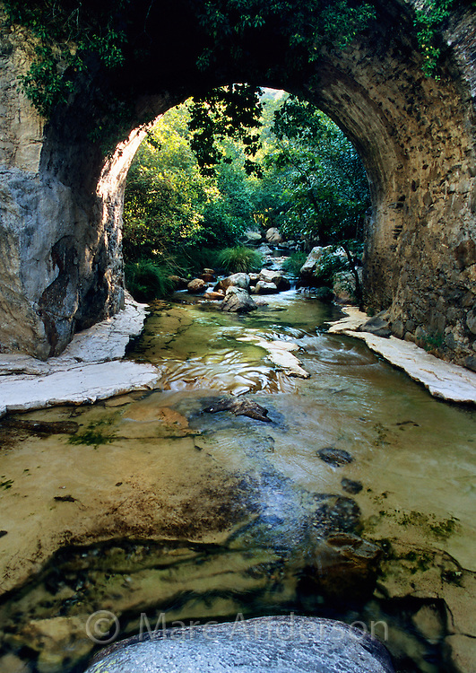 Beautiful clear water flowing in a stream under an old bridge, Valle de las Batuecas, Extremadura, Spain