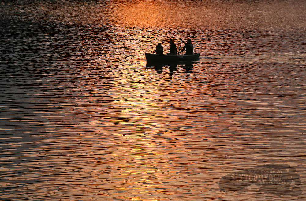 Photo by Gary Cosby Jr.  People paddle a canoe into the setting sun on Tupper Lake in Adirondack Park near Tupper Lake, New York.