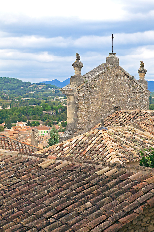 Tile roofs and a church facade frame the Provencal countryside from Upper Town Vaison-la-Romaine. Provence, France.