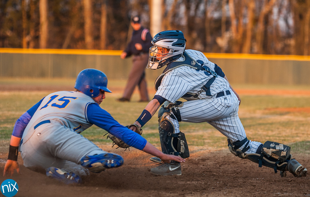 Hickory Ridge catcher Austin Greco tries to tag out Mount Pleasant's Justin Green at home plate Friday night at Hickory Ridge High School in Harrisburg. The Ragin' Bulls won the game 13-4.