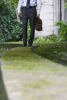 Businessman walking on wall in park low section