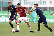 AC Milan's Turkish midfielder Hakan Calhanoglu takes the ball past AS Roma's Italian midfielder Lorenzo Pellegrini as AS Roma's Italian midfielder Bryan Cristante looks on during the Serie A match at Giuseppe Meazza, Milan. Picture date: 28th June 2020. Picture credit should read: Jonathan Moscrop/Sportimage
