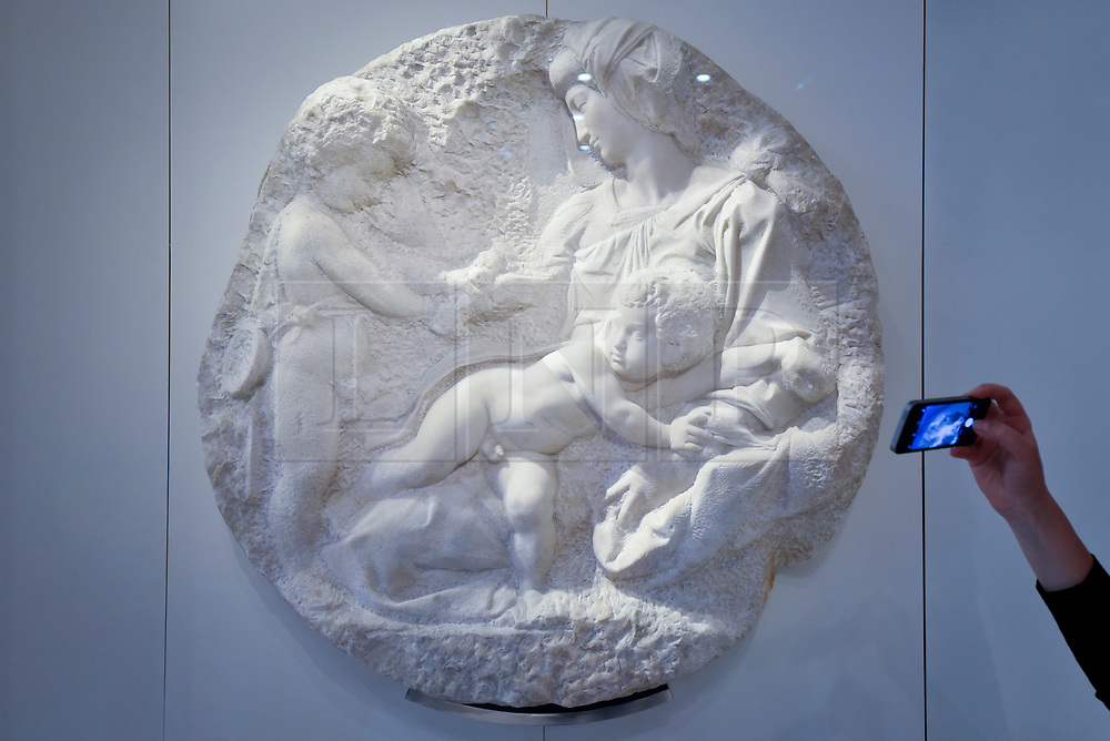 """© Licensed to London News Pictures. 14/05/2018. LONDON, UK. A visitor photographs """"The Virgin and Child with the infant St. John"""", 1504-05, by Michelangelo, considered one of the greatest sculptural works in the UK, at a photocall for the opening of the new Royal Academy of Arts (RA) in Piccadilly.  As part of the celebrations for its 250th anniversary year, redevelopment has seen the RA's two buildings, 6 Burlington Gardens and Burlington House, united into one extended campus and art space extending from Piccadilly to Mayfair.  Photo credit: Stephen Chung/LNP"""