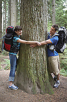 Couple hugging tree in forest