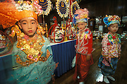 Three boys dressed up as princes in remembrance of the Buddha stand inside a temple during Poy Sang Long, the ordination of novice monks in Mae Hong Son, Thailand. April 2003.