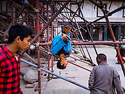 05 MARCH 2017 - KATHMANDU, NEPAL: Boys play on scaffolding that is holding up the wall of the Hanuman Dhoka Palace on Durbar Square in Kathmandu, a UNESCO World Heritage Site badly damaged in the 2015 earthquake. Much of Kathmandu is now a construction site because of rebuilding  two years after the earthquake of 25 April 2015 that devastated Nepal. In some villages in the Kathmandu valley workers are working by hand to remove ruble and dig out destroyed buildings. About 9,000 people were killed and another 22,000 injured by the earthquake. The epicenter of the earthquake was east of the Gorka district.     PHOTO BY JACK KURTZ