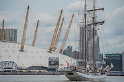 The JR Tolkien passing the O2 - Royal Greenwich Tall Ships Festival with a fleet of square rigged ships moored on the Thames at Greenwich and Woolwich. The fleet includes two of the biggest Class A Tall Ships - the Dar Mlodziezy and Santa Maria Manuela - which are moored on Tall Ships Island in the river off Greenwich. Tall Ships Festival Day on Saturday 29 August featured free family entertainment and the chance to enjoy a taste of life on the high seas.