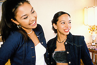 Two young Asian women laughing and smiling.